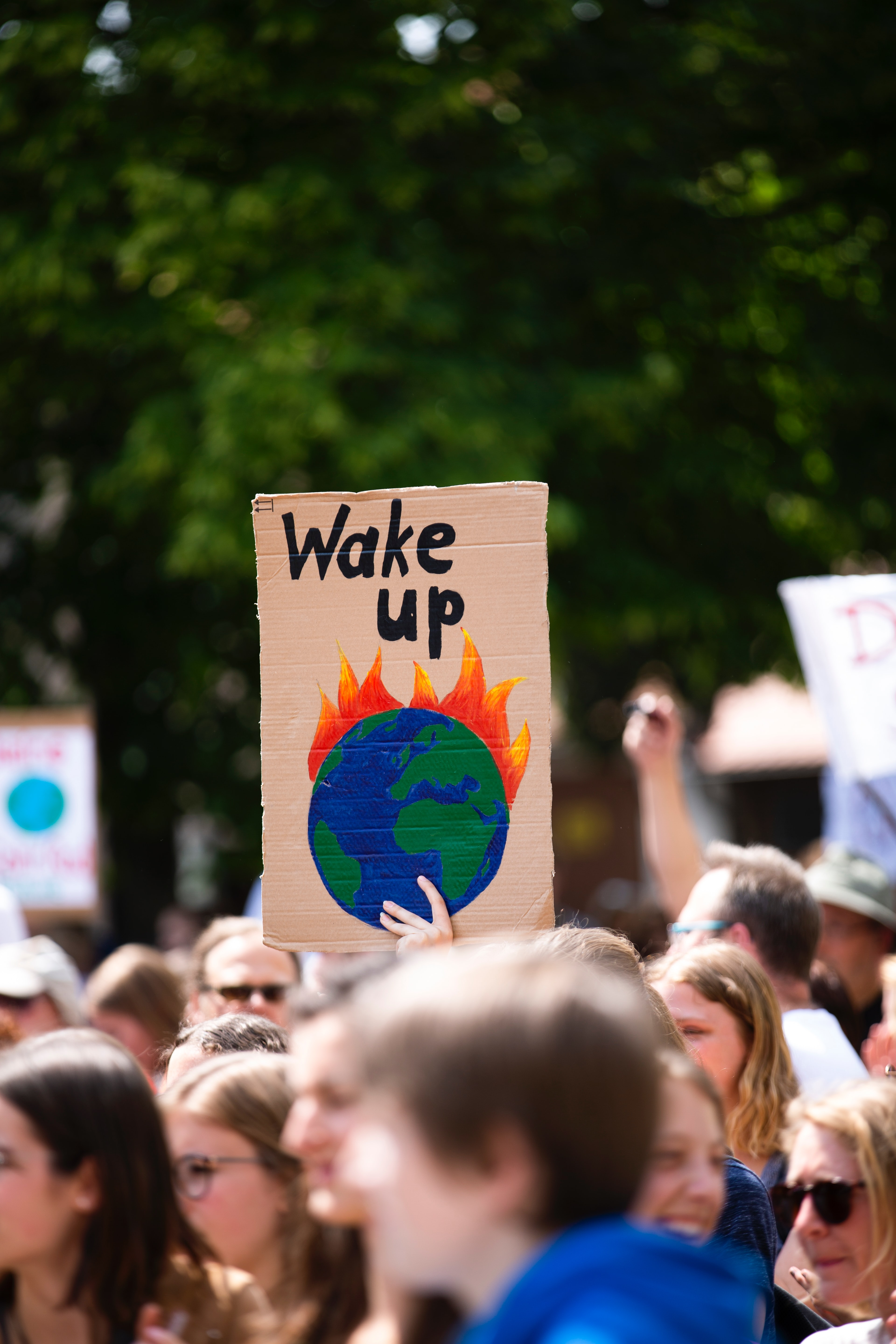 "Photo of protest sign with an image of a burning earth with the words, ""Wake up."" Image courtesy of Markus Spiske via Unsplash."