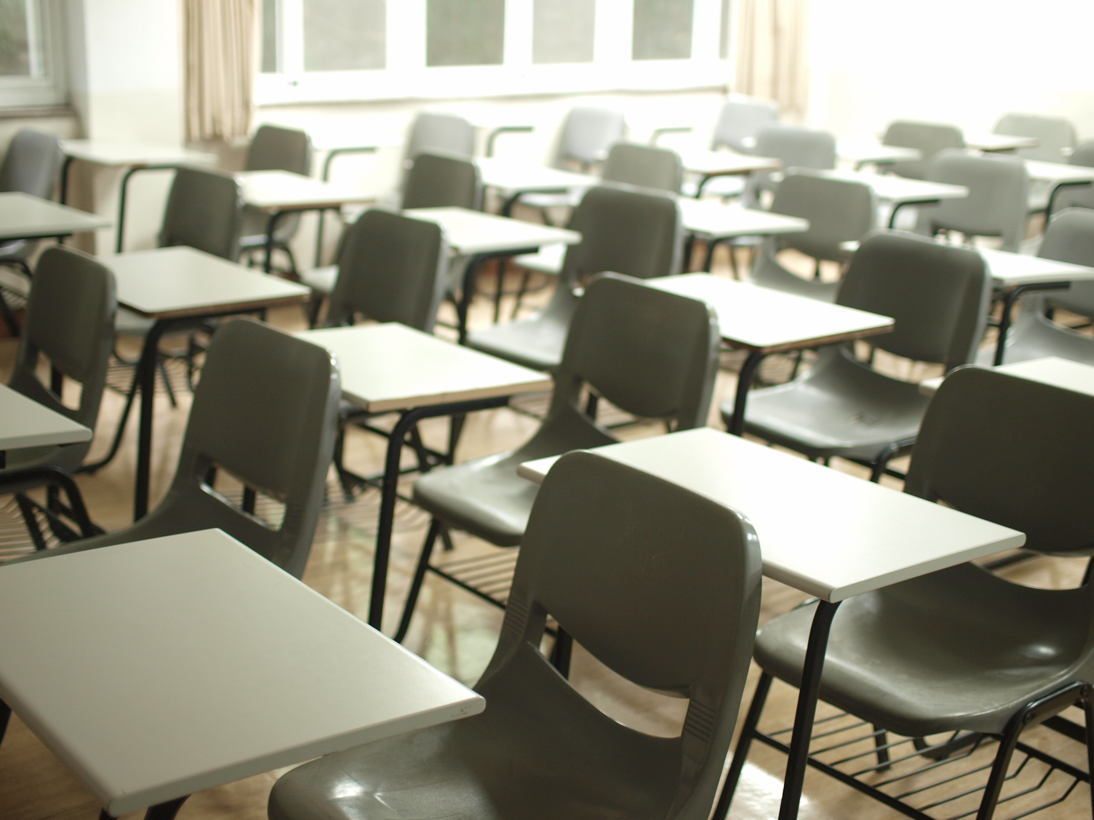 Rows of chairs in an empty classroom. Photo courtesy of MChe Lee via Unsplash.