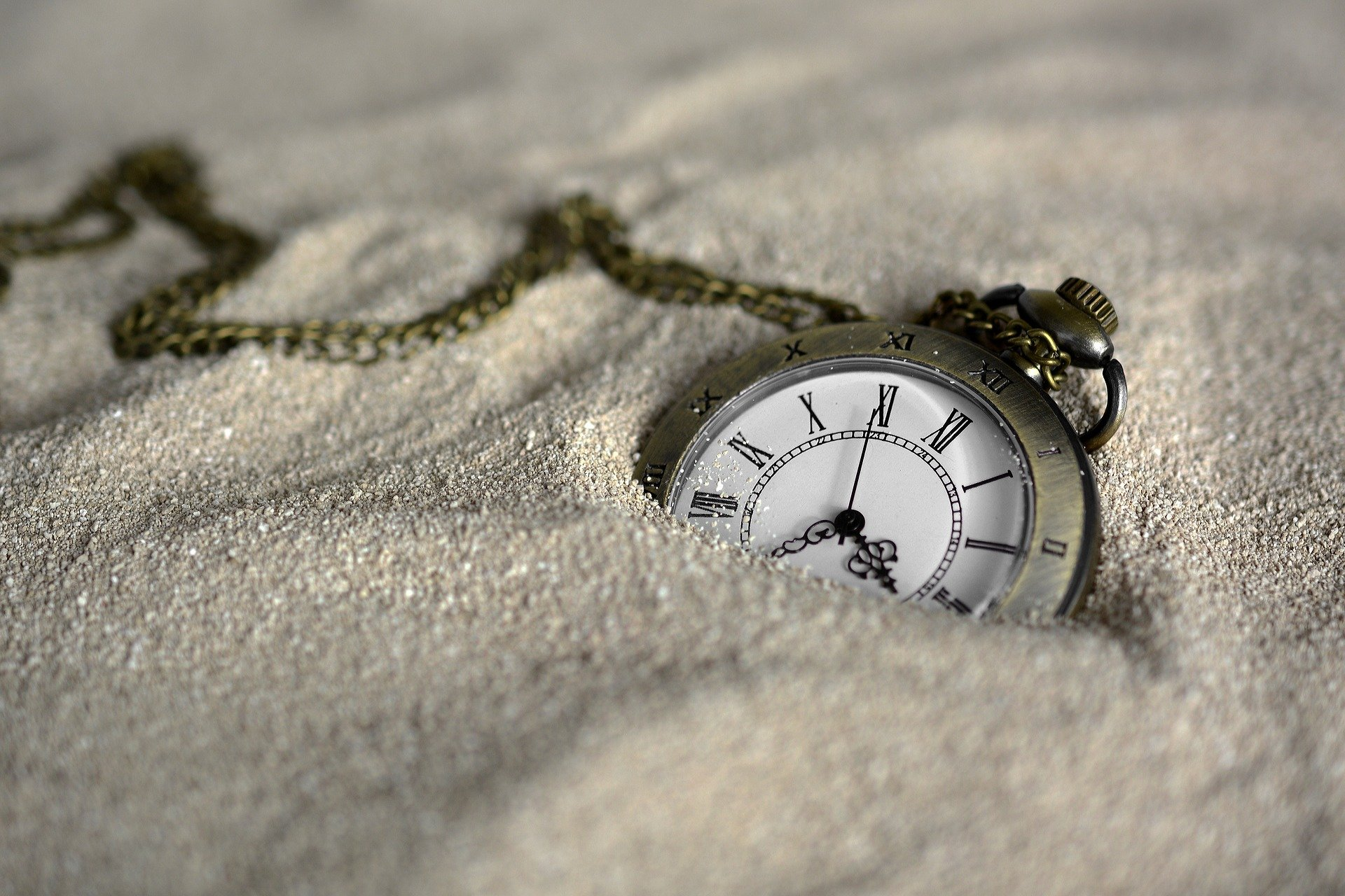 Pocket Watch lays buried in the sand. Photo courtesy of anncapictures on Pixabay.