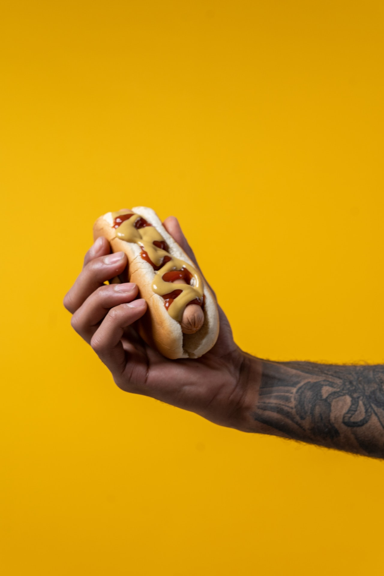 A hand holds a hotdog with mustard and other toppings against a yellow background. Photo courtesy of Cottonbro on Pexels.