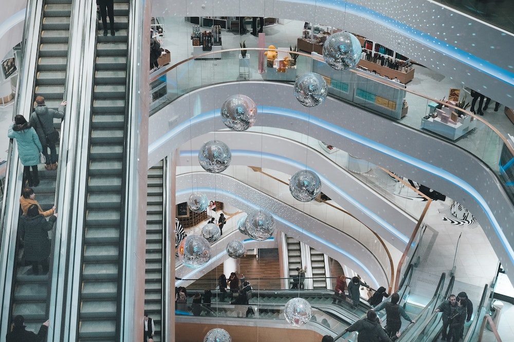 People using escalators at a busy mall, with disco balls hanging from the ceiling. Photo courtesy of Victor Xok on Unsplash.
