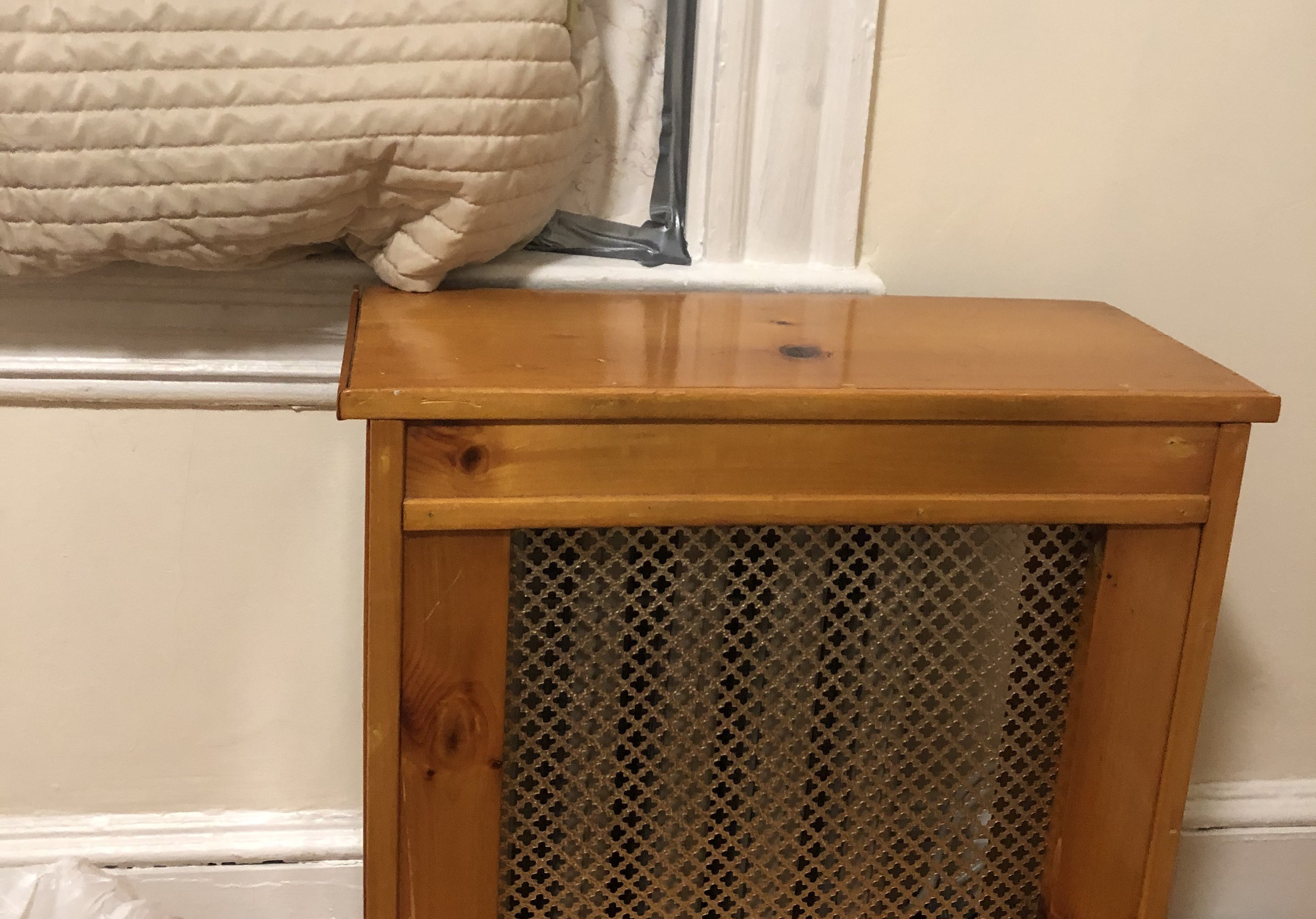A wooden radiator box in front of a window blocked by blankets in the author's home. Photo courtesy of the author.