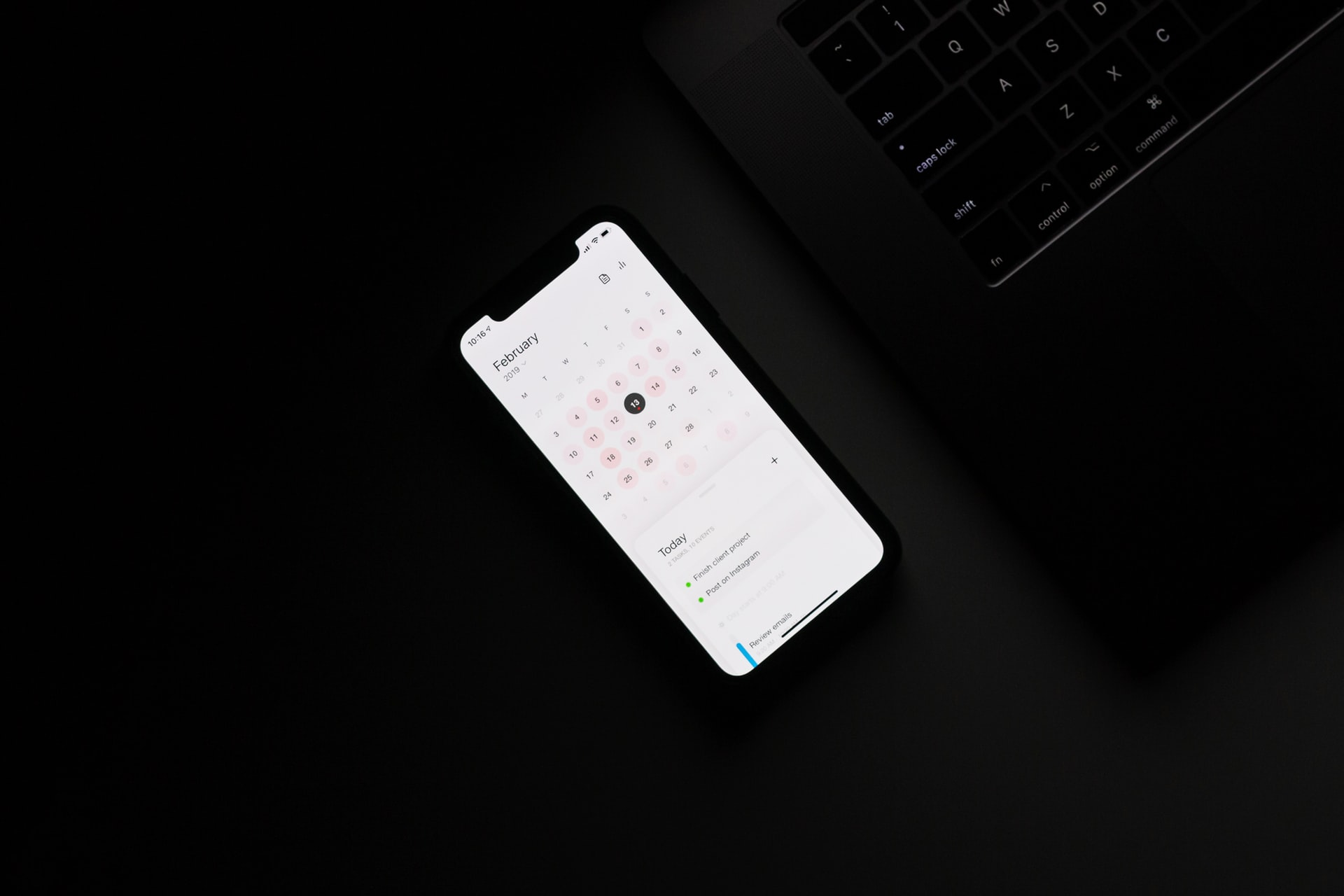 Black Android phone displays a calendar app in a dark room. Photo courtesy of Ales Nesetril on Unsplash.