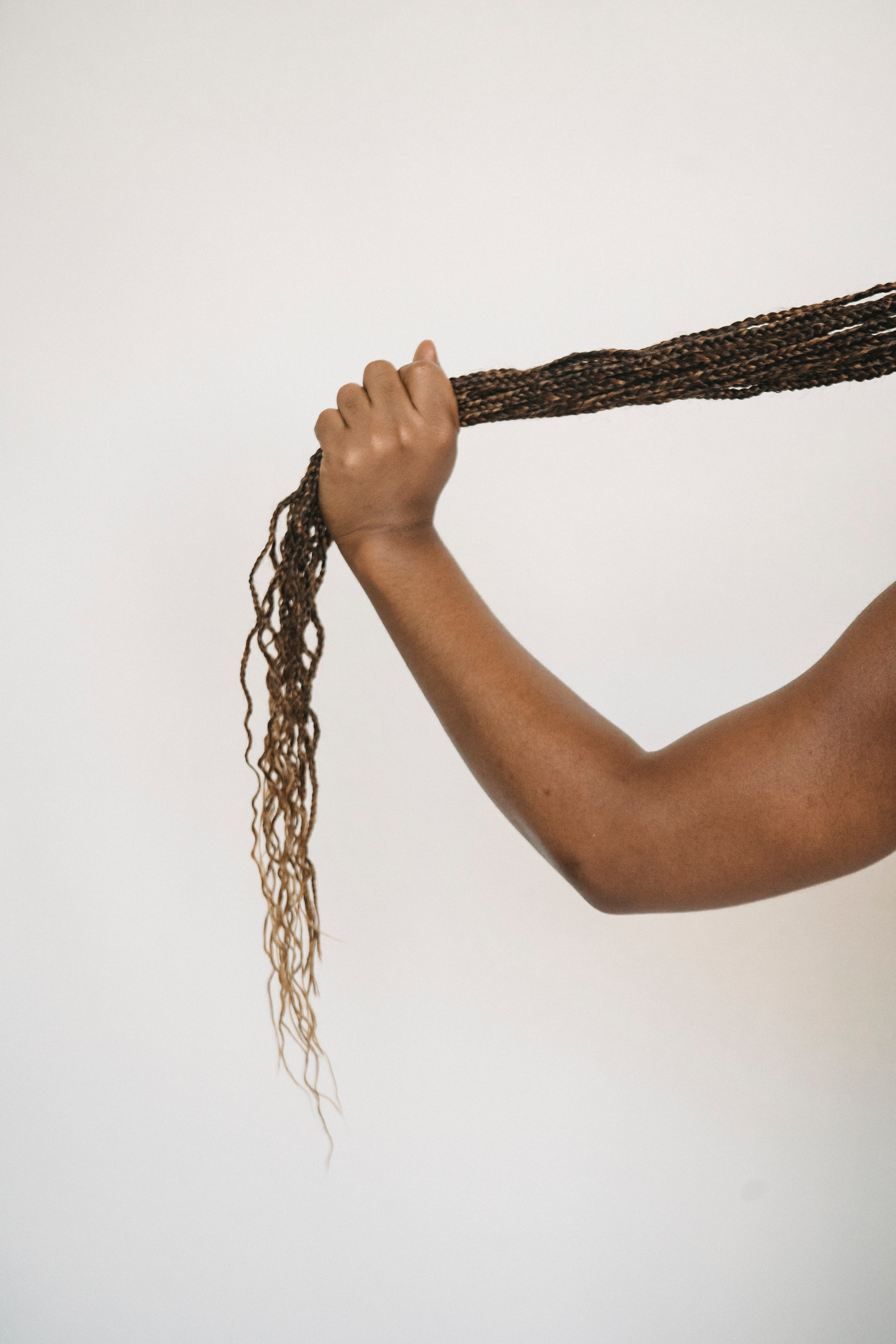 A hand holding out box braids. Photo courtesy of Armin Rimoldi from Pexels.