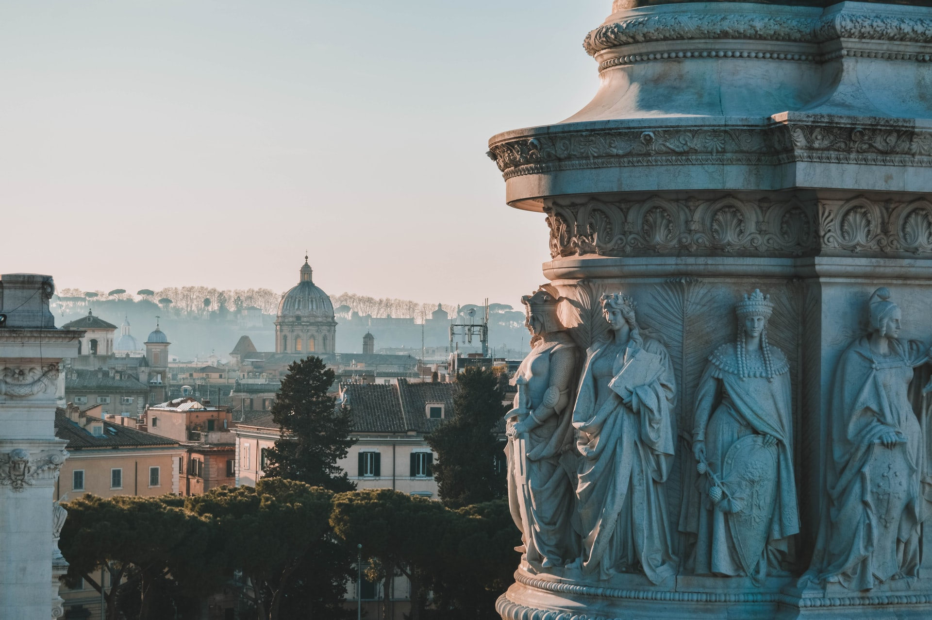 Statues of people carved into a building in Rome, Italy. Photo courtesy of Carlos Ibáñez on Unsplash.