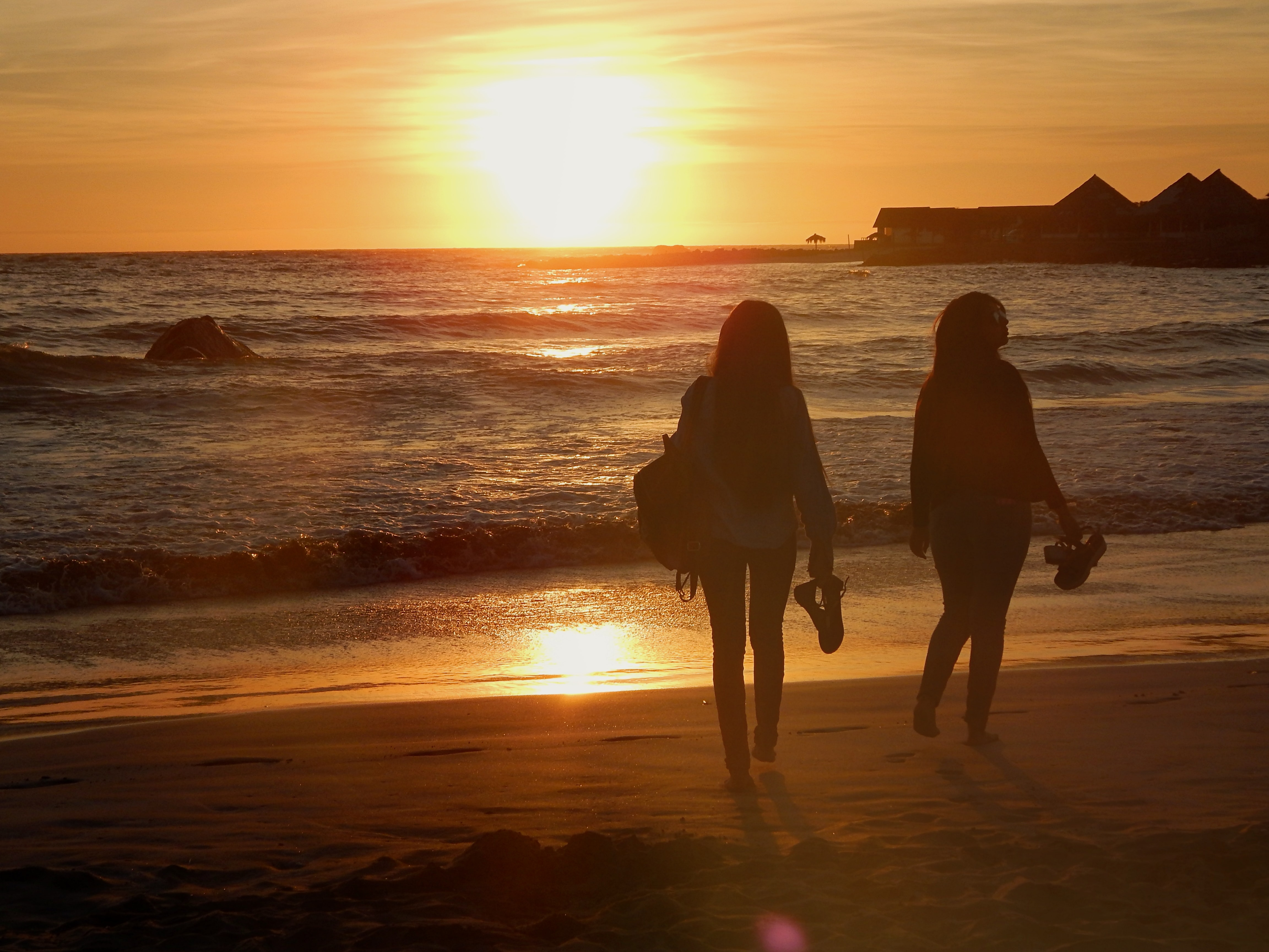 Silhouettes of people walking along the beach at sunset. Photo courtesy of Jael Rodriguez on Unsplash.