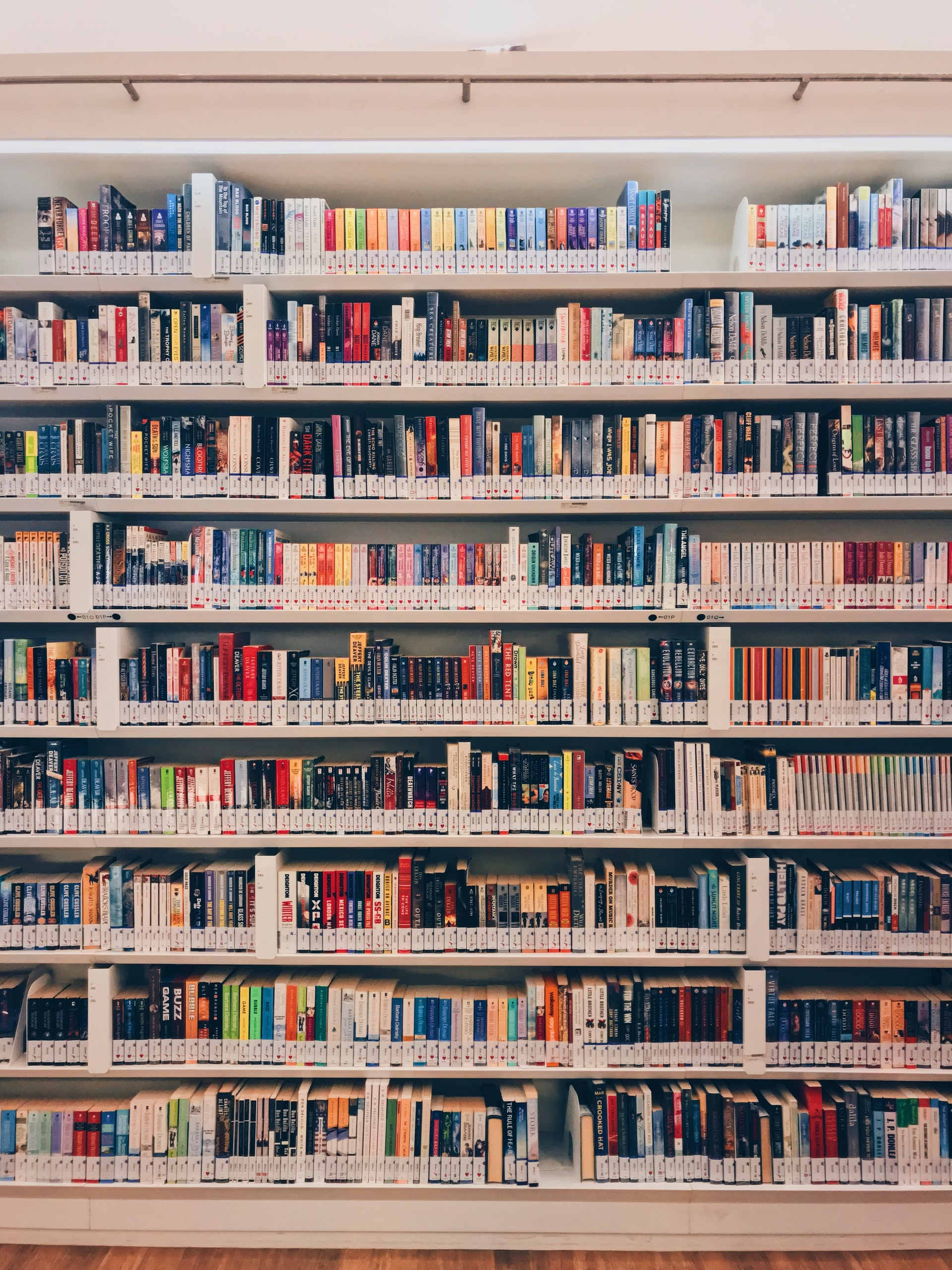 Shelves of multicolored library books. Photo courtesy of Zaini Izzuddin on Unsplash.