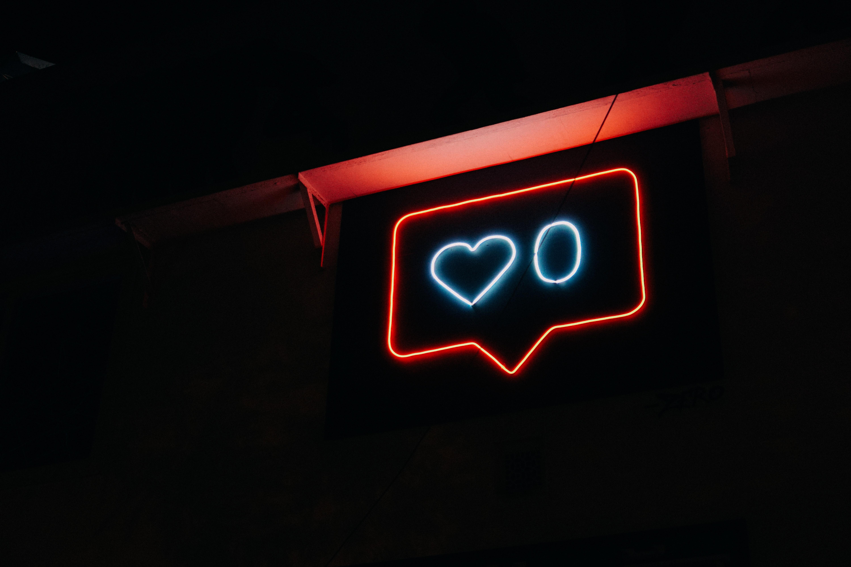 "Neon sign of an Instagram ""like."" Photo courtesy of Prateek Katyal on Unsplash."