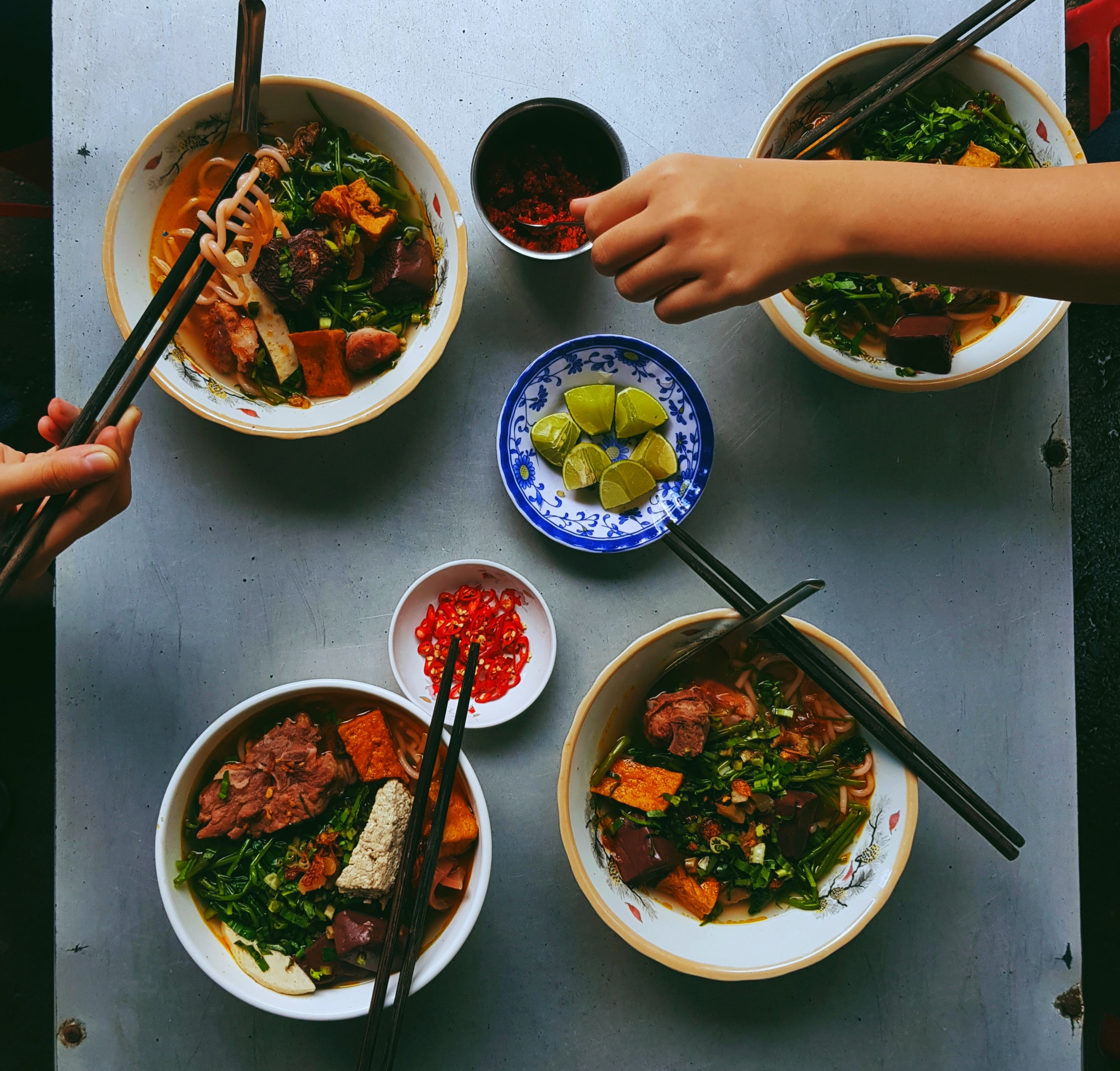 Photo of soup bowls and side dishes on a table with hands reaching toward the food. Image Courtesy of Trung Bui via Unsplash.