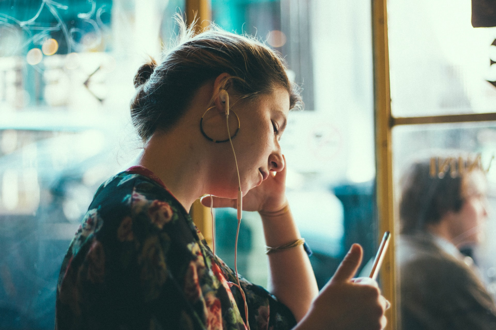 Woman with headphones in, staring into space. Photo courtesy of Siddarth Bhogra on Unsplash.