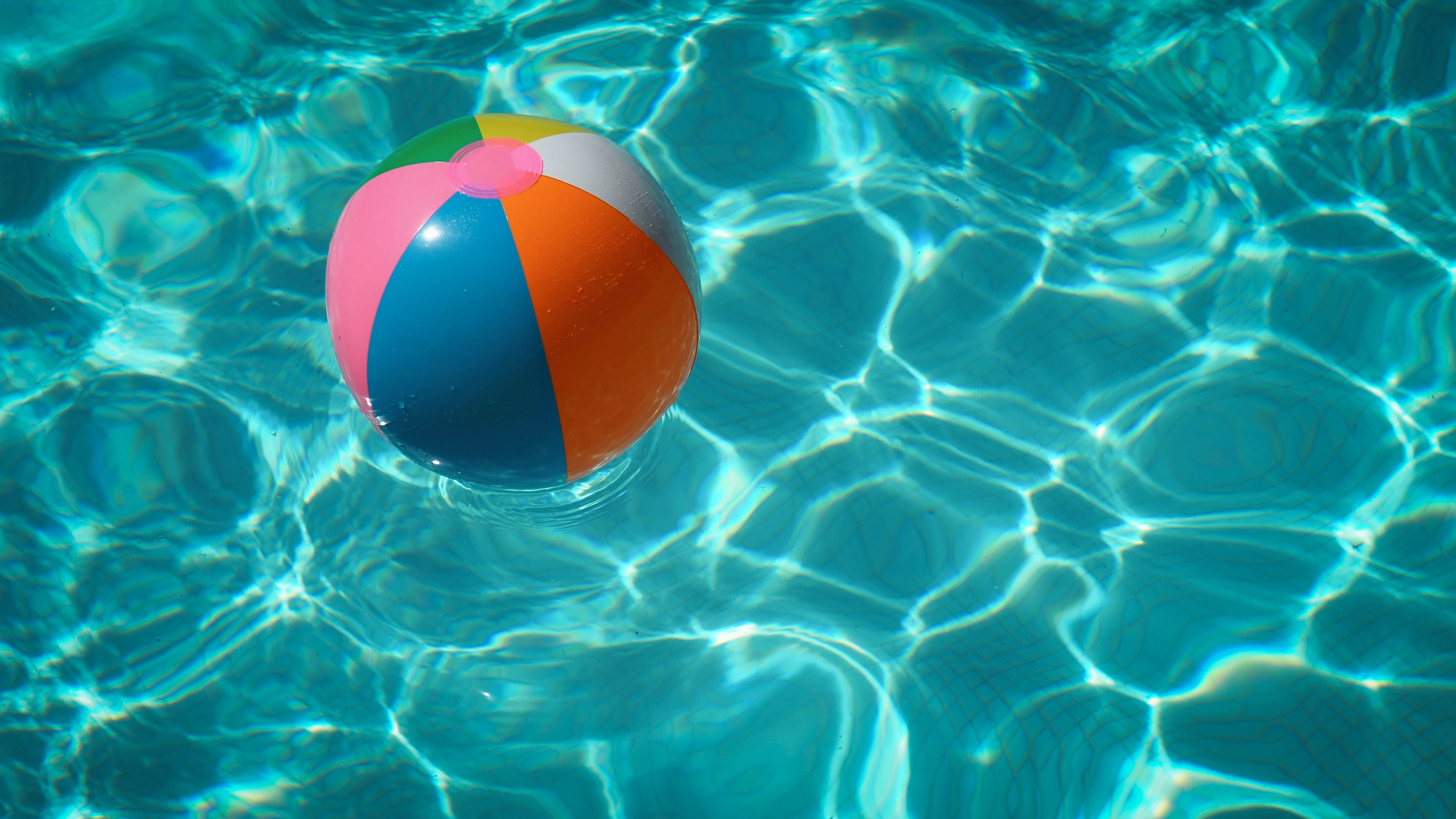 A multi-colored beach ball floats in the pool. Photo courtesy of Raphaël Biscaldi on Unsplash.