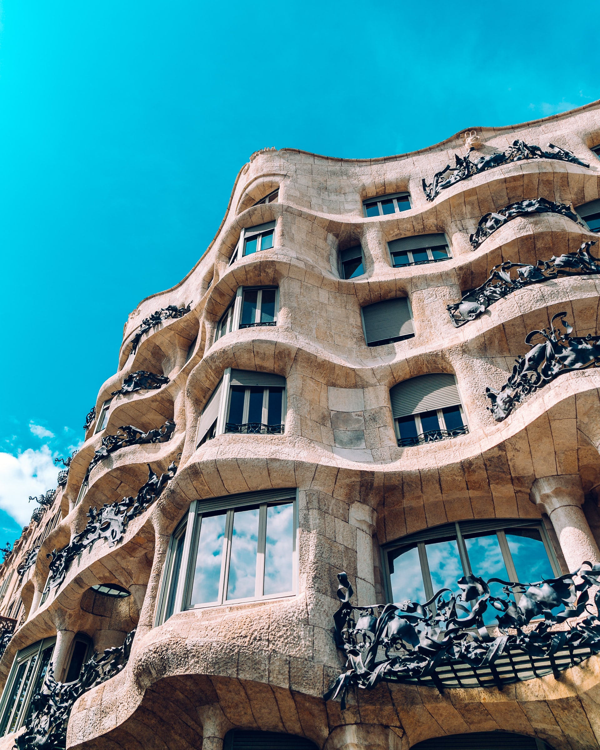 "Antoni Gaudi's curved, beige concrete ""La Pedrera"" building in Barcelona, Spain. Photo courtesy of Florencia Potter on Unsplash."