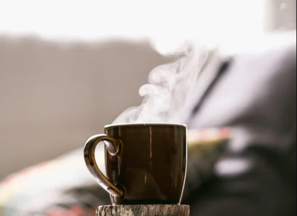 Photo of a dark mug on a coaster with steam coming out of it. Image courtesy of Tim Foster via Unsplash.