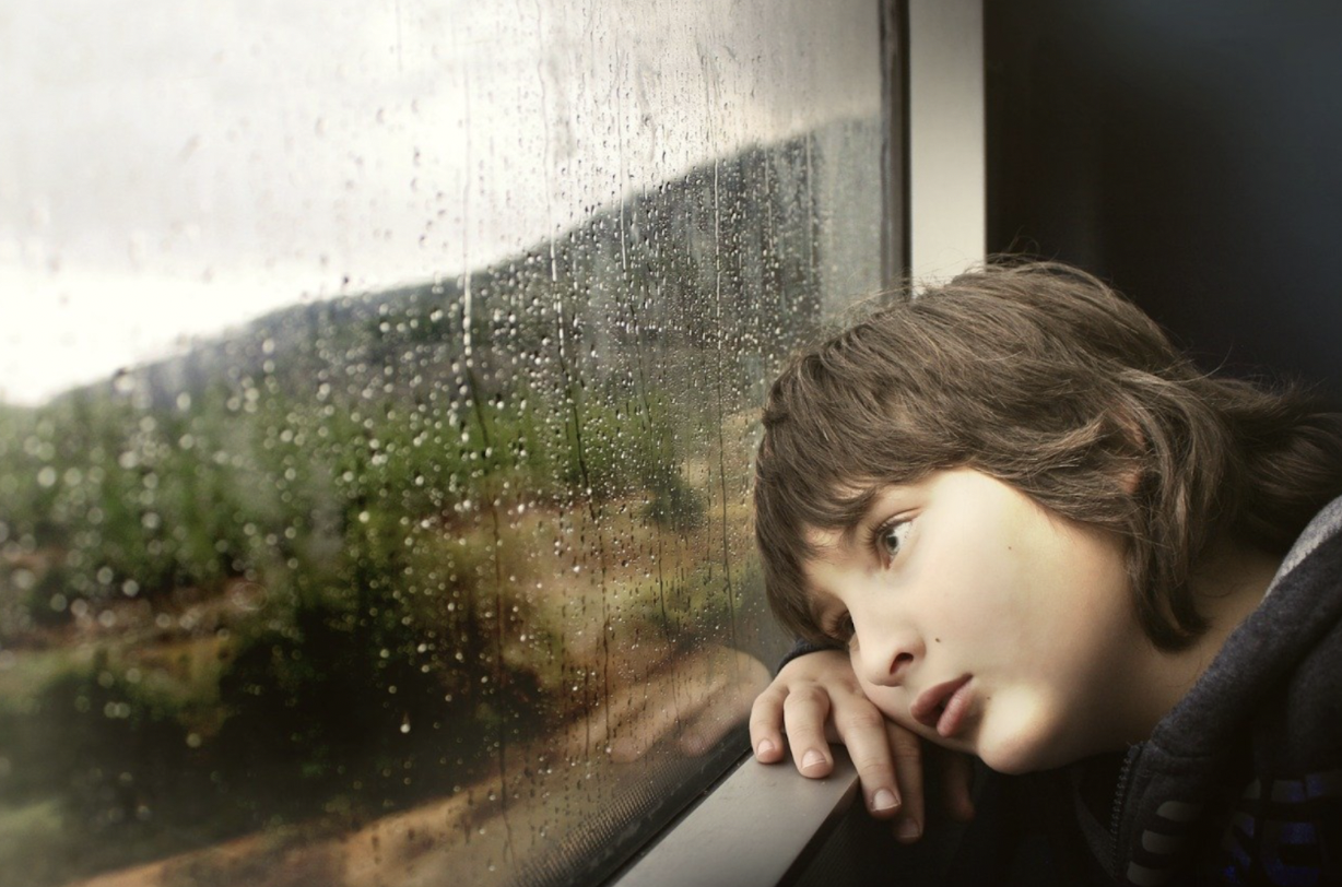 Photo of a young person leaning against a window sill, looking outside. Image via Pixabay.