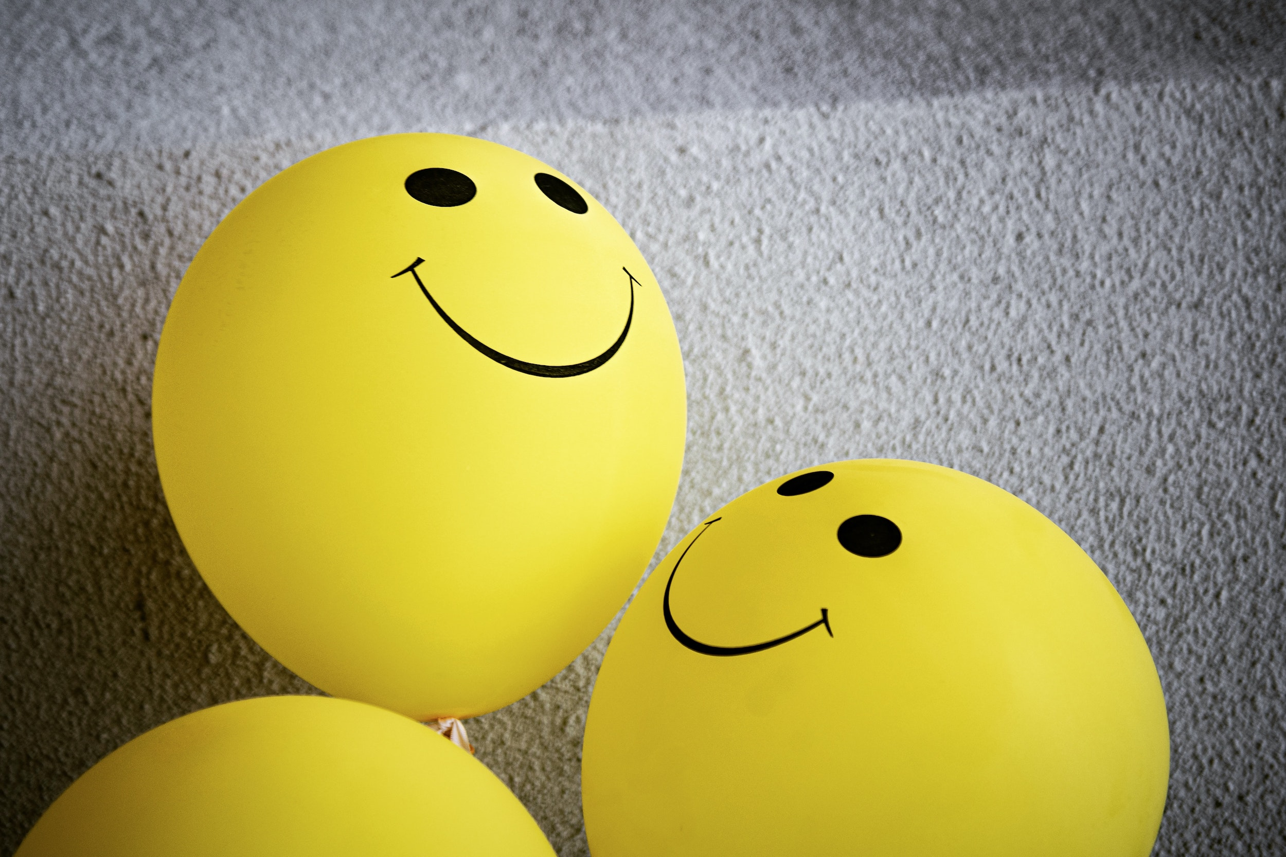 Three yellow balloons with smiley faces on them against a grey backdrop. Photo courtesy of Tim Mossholder on Unsplash.
