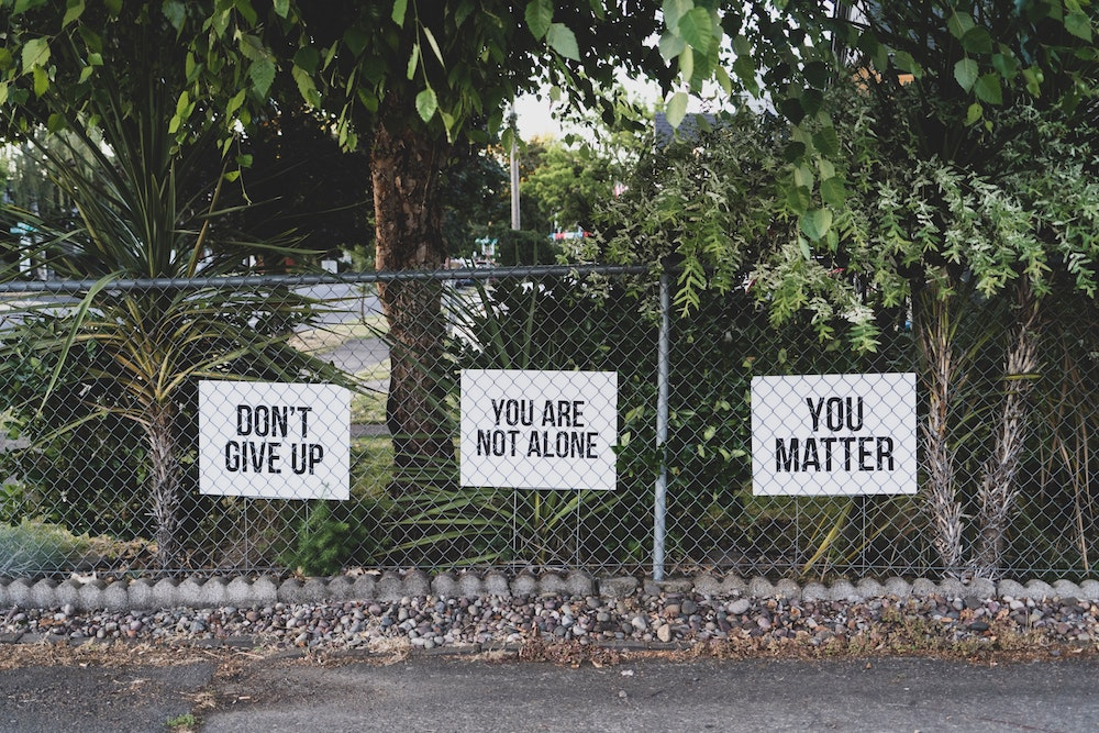 "Three signs behind a fence that read, ""Don't give up,"" You are not alone"" and ""You matter."" Photo courtesy of Dan Meyers on Unsplash."