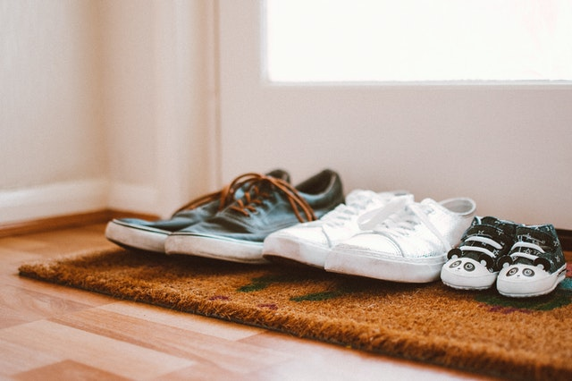Three pairs of shoes — one large grey pair of Vans with brown laces, one white pair of Vans with white laces, and one baby-sized pair of black and white sneakers. Photo courtesy of Lisa Fotios on Pexels.