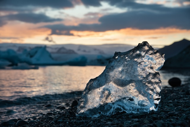 A segment of glacial ice slowly melts on the cold beach of a glacial lagoon in Iceland. Photo courtesy of Joseph Vary on Unsplash.