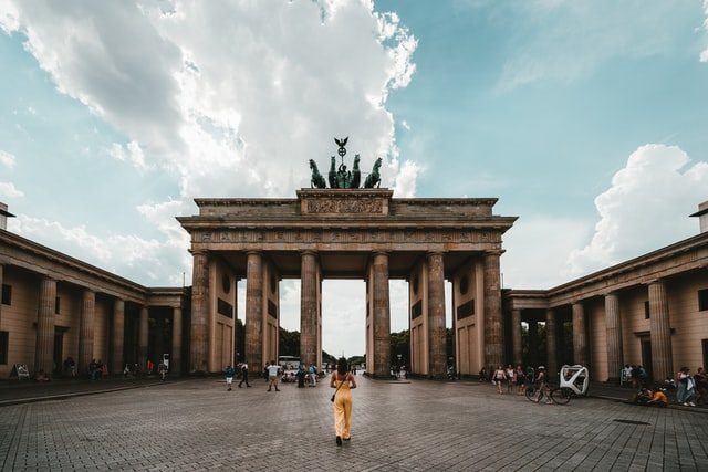 Woman wearing yellow jumpsuit stands in front of Brandenburg Gate in Berlin, Germany. Photo courtesy of Claudio Schwarz on Unsplash.