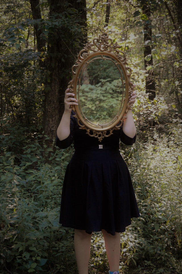 Woman holding mirror against her head and face in the middle of a forest, with the green forest reflecting on the mirror. Photo courtesy of Tasha Kamrowski on Unsplash.
