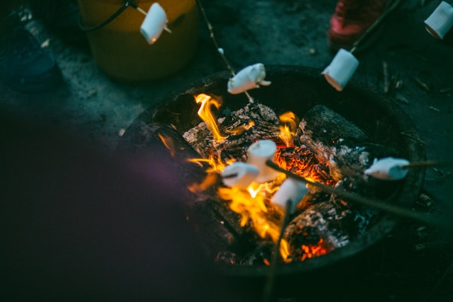 People grilling marshmallows on sticks over a wooden fire. Photo courtesy of Josh Campbell on Unsplash.