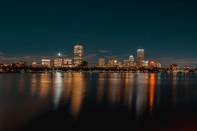 View of the Boston skyline's buildings lit up at night, reflecting on water. Photo courtesy of Osman Rana on Unsplash.