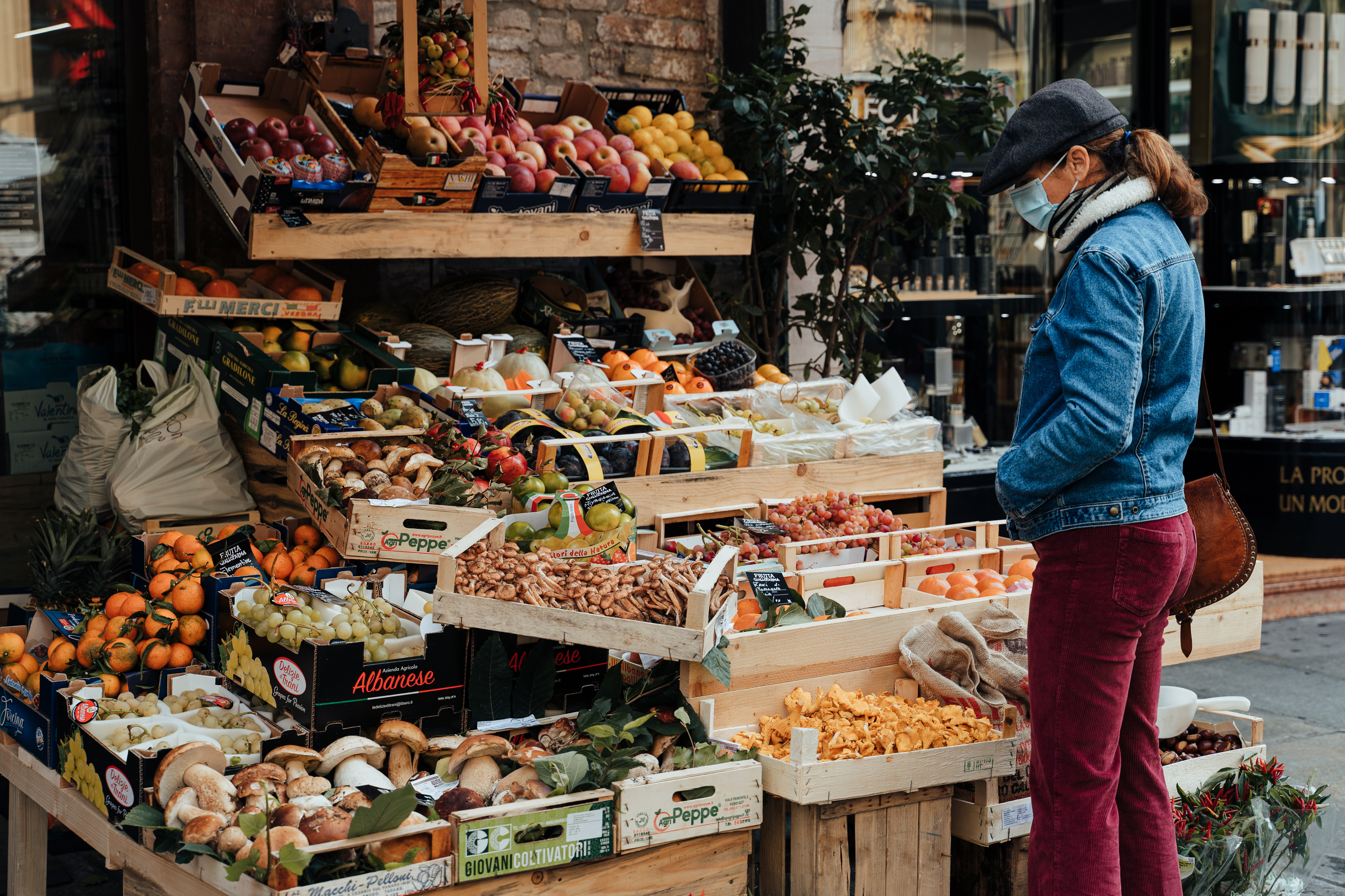 Photo of a person wearing a mask looking at produce outdoors. Image courtesy of Gabriella Clare Marino via Unsplash.