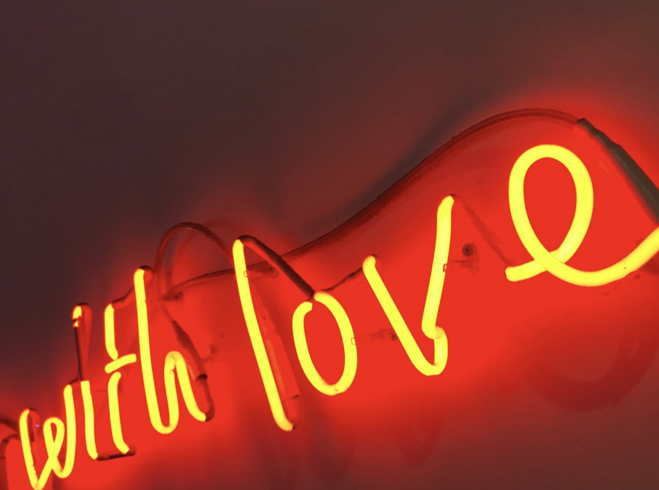 "Photo of a red neon sign that reads, ""with love."" Image courtesy of author."
