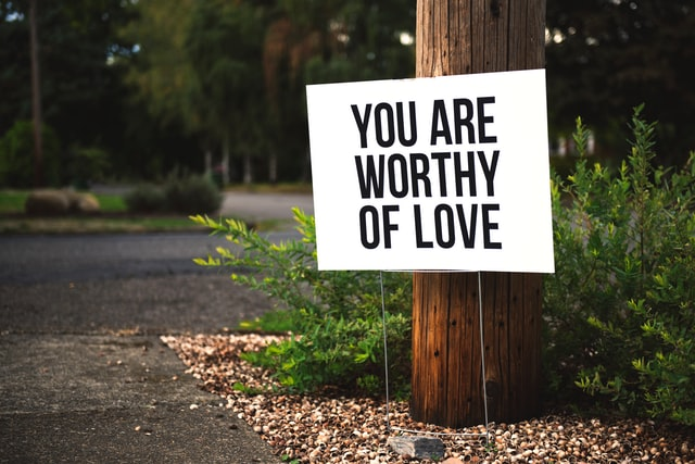"""A lawn sign that reads """"You are worthy of love."""" Photo courtesy of Tim Mossholder on Unsplash."""