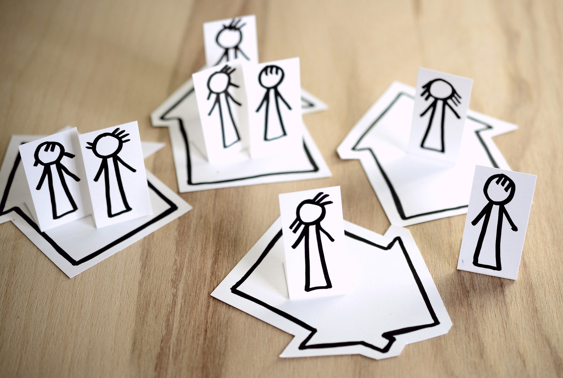 Photo of stick figures propped up on hand-drawn houses. Image by @congerdesign from Pixabay