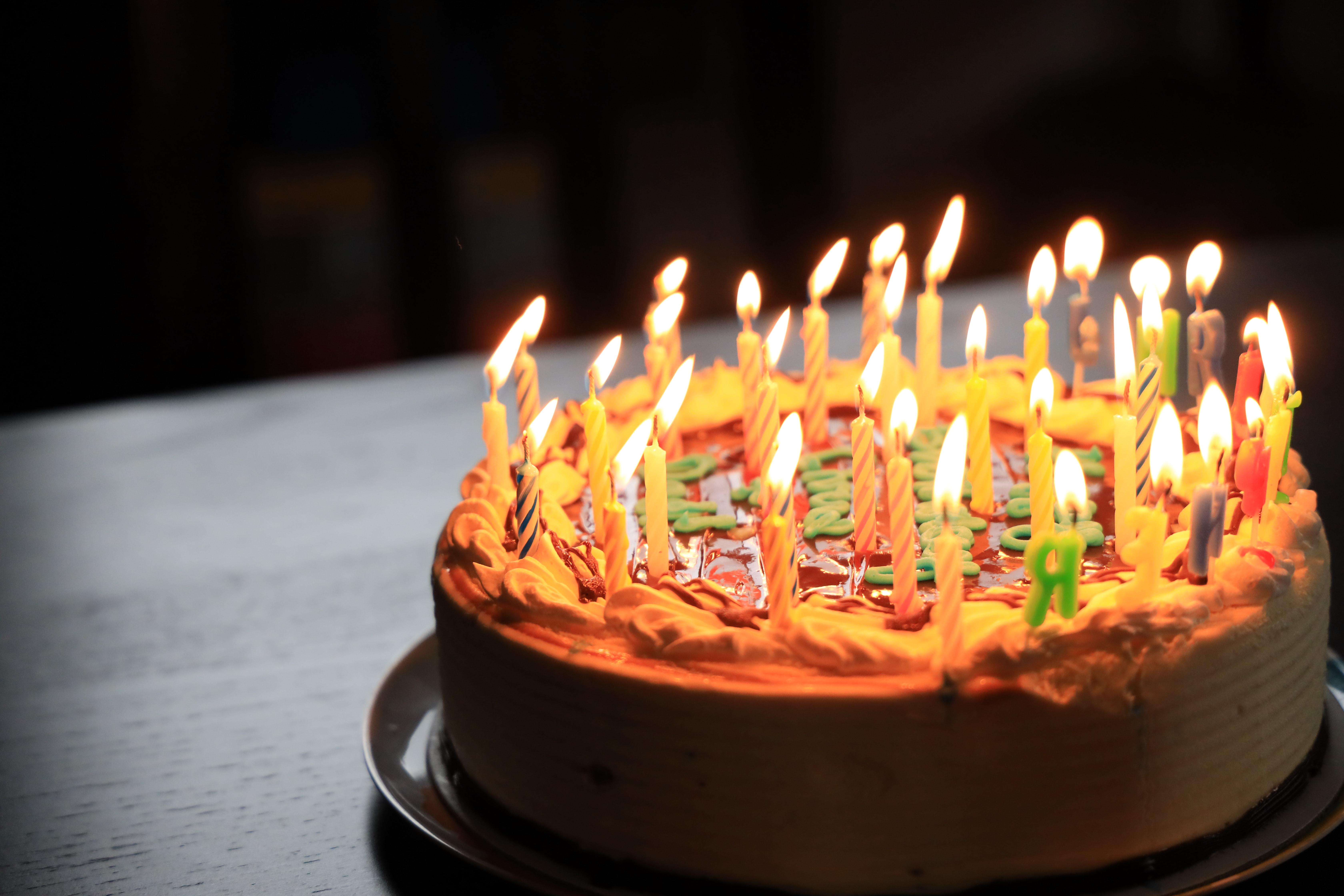 Photo of a birthday cake with lit candles on top. Image courtesy of Richard Burlton via Unsplash.