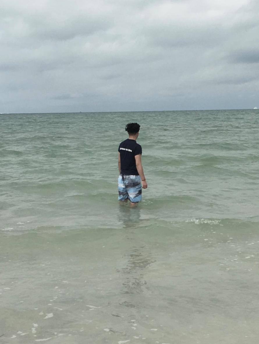 A person standing knee-deep in the ocean. Photo courtesy of the author.