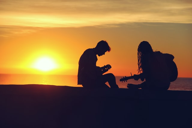 Silhouettes of two people playing guitar on the beach at dusk. Photo courtesy of Mike Giles on Unsplash.