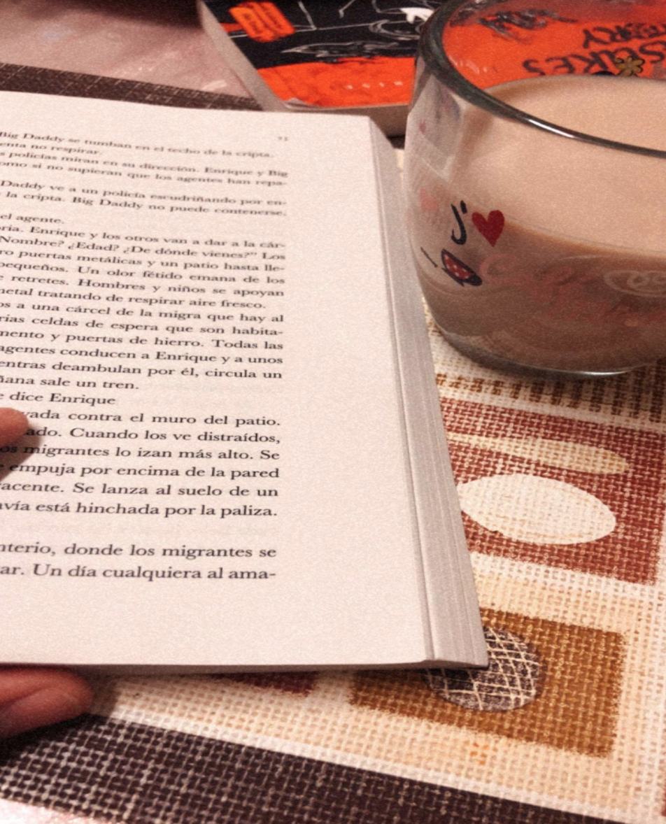 An open book with words written in Spanish next to a drink in a clear glass. Photo taken by the author.
