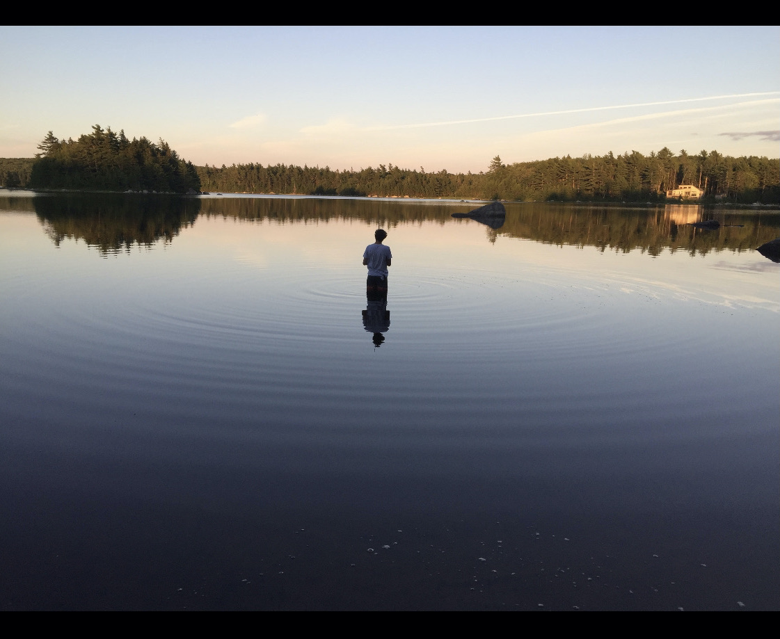 A person standing in the middle of a lake at dusk. Photo courtesy of the author.