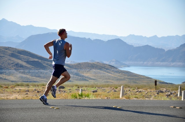 Man running in athletic clothes on a road in front of a mountainous landscape. Photo courtesy of Pixabay on Pexels.