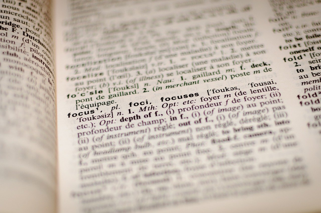 """Open dictionary page blurred besides the word """"focus"""" and its definition."""