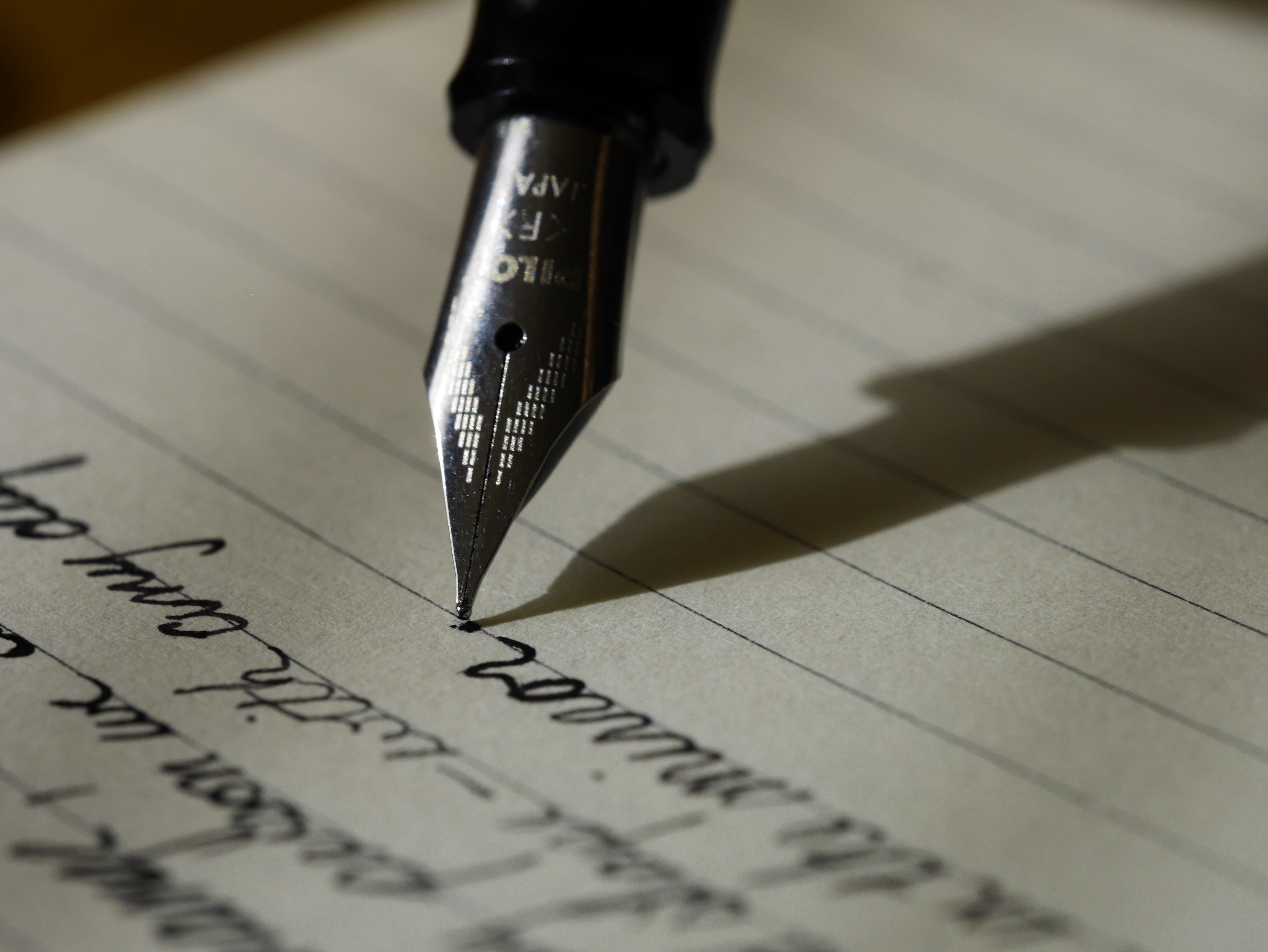Image of a black ink pen writing on lined paper. Photo courtesy of Aaron Burden on Unsplash.