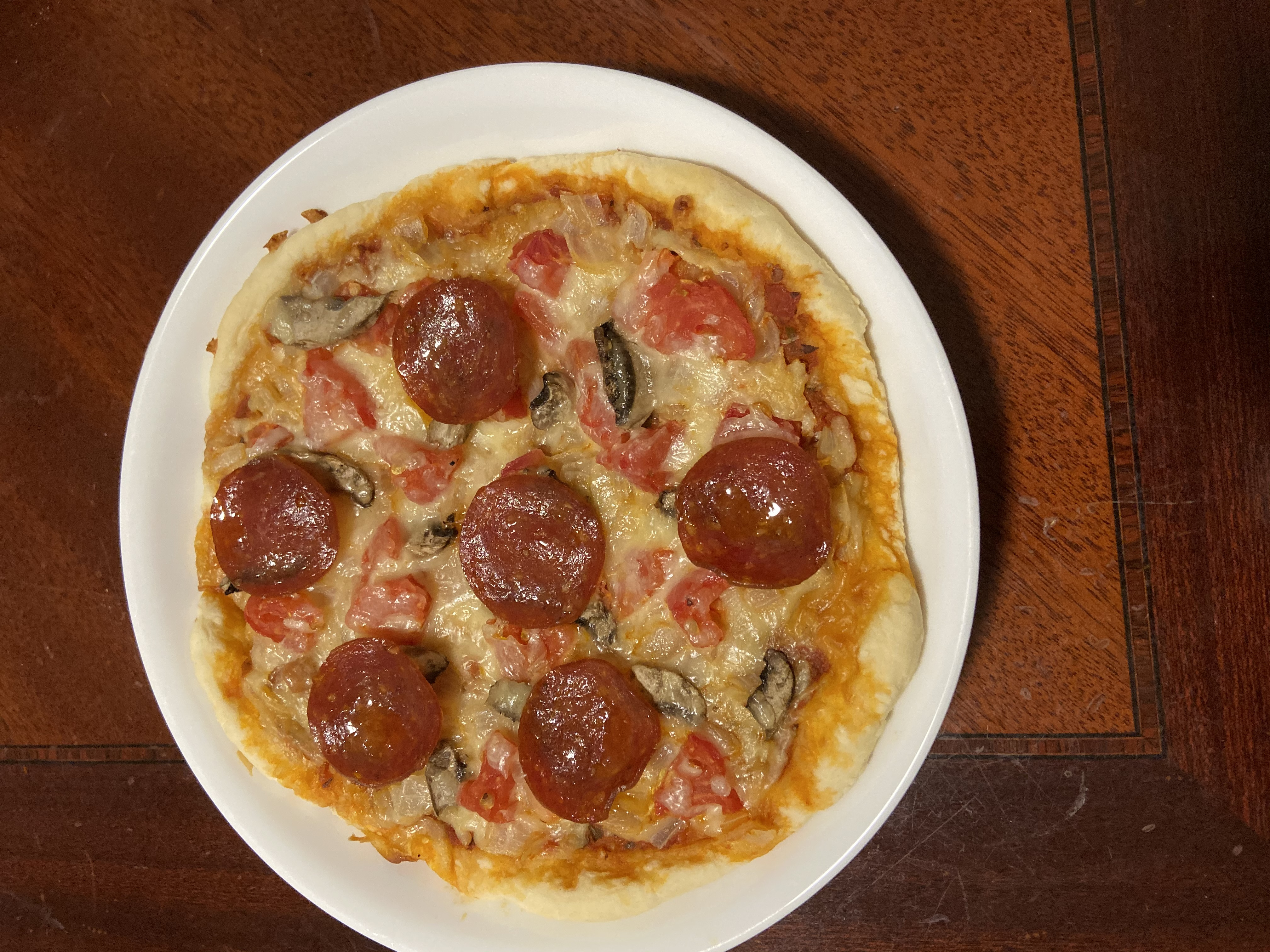A homemade pizza topped with cheese, pepperoni, mushrooms and tomatoes. Photo taken by the author.