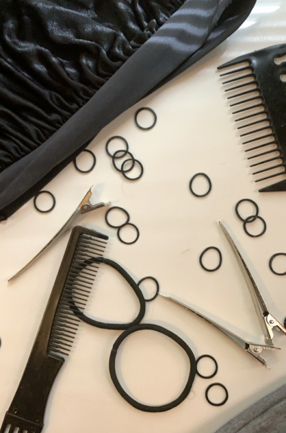 Haircare products, including ponytails, rubber bands, combs, clips, and a bonnet. Photo courtesy of the author.