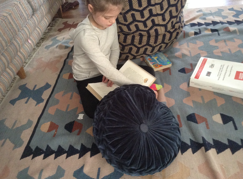 The author, when she was younger, reading a book on the floor. Photo courtesy of the author.