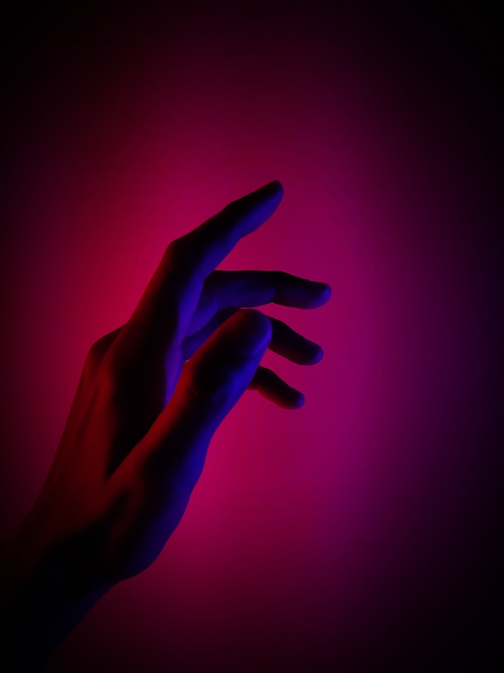 A hand reaching out under lighting in the colors of the bisexual flag: purple, blue, and magenta. Photo courtesy of Nitish Goswami on Unsplash.