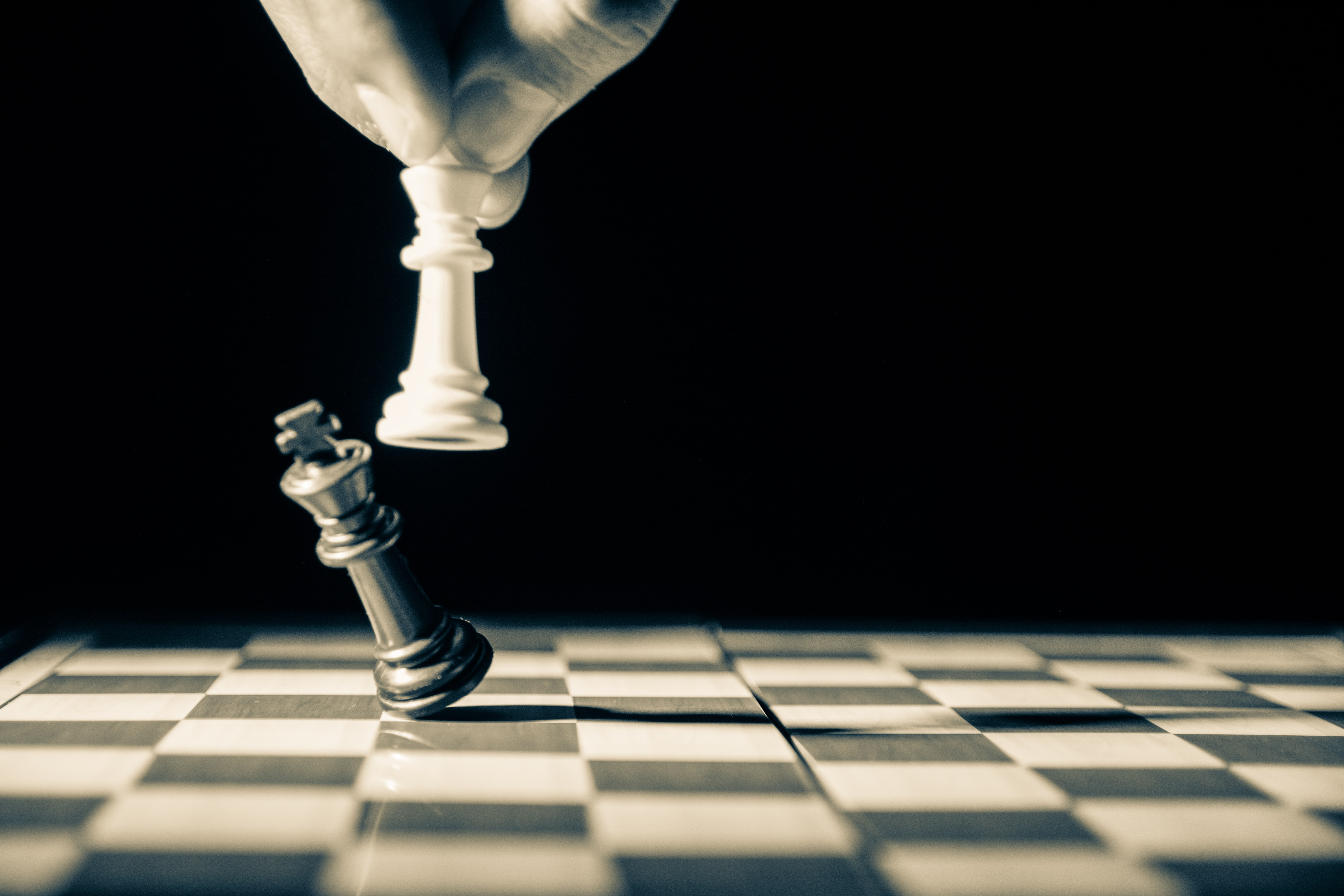 A white chess piece knocking a black chess piece off the game's board. Photo courtesy of GR Stocks on Unsplash.