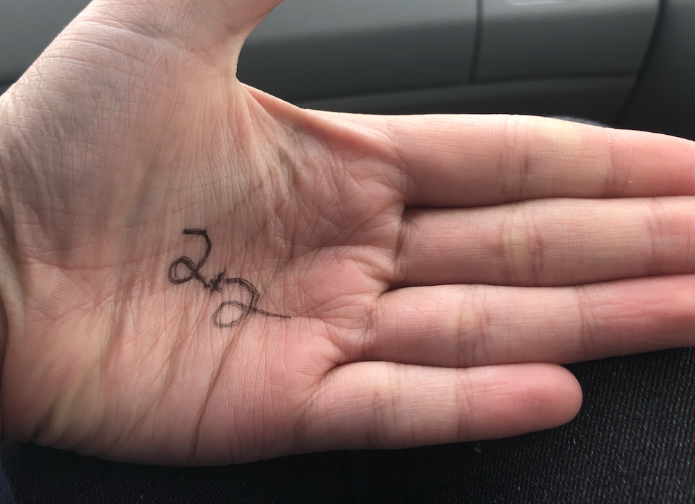 """""""2 x 2"""" written on a hand in black ink. Photo taken by the author."""