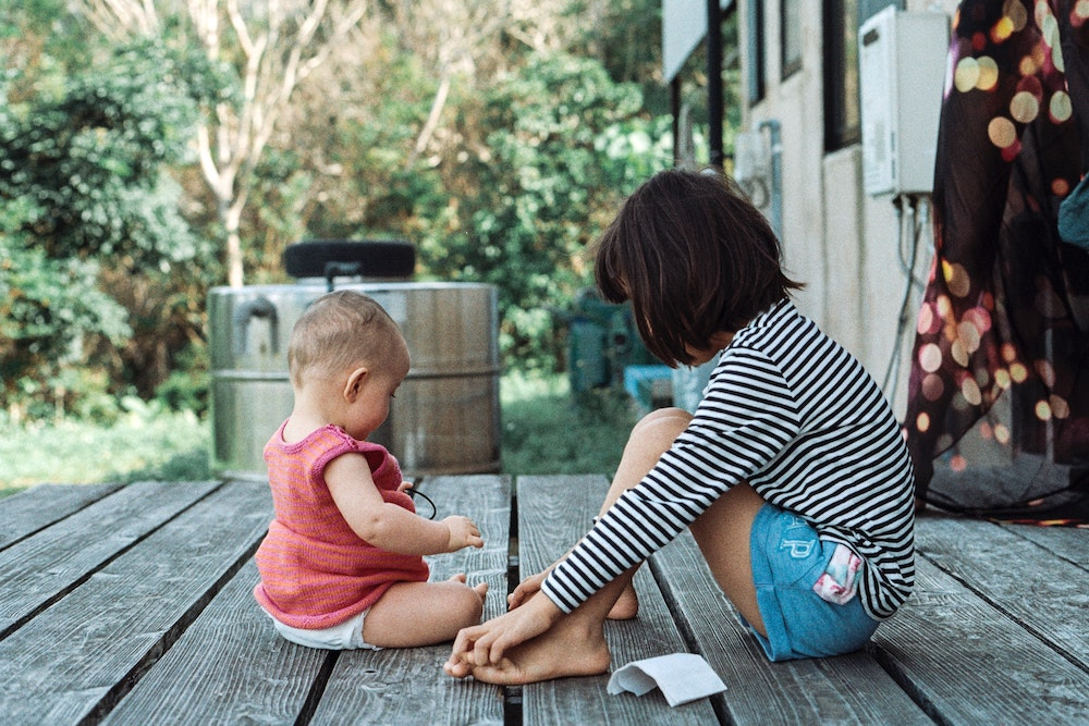 A child wearing a striped shirt sits next to a baby outside. Photo courtesy of Jens Johnsson on Unsplash.