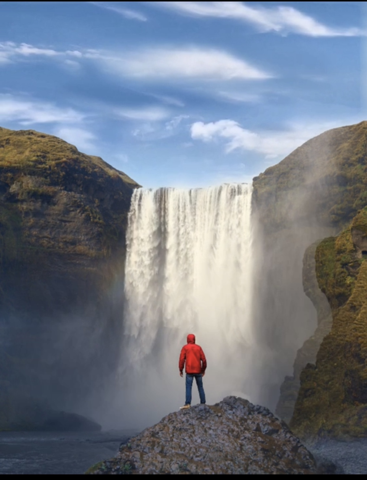 Photo of the author standing in front of a waterfall in a red rain jacket. Photo courtesy of the author.