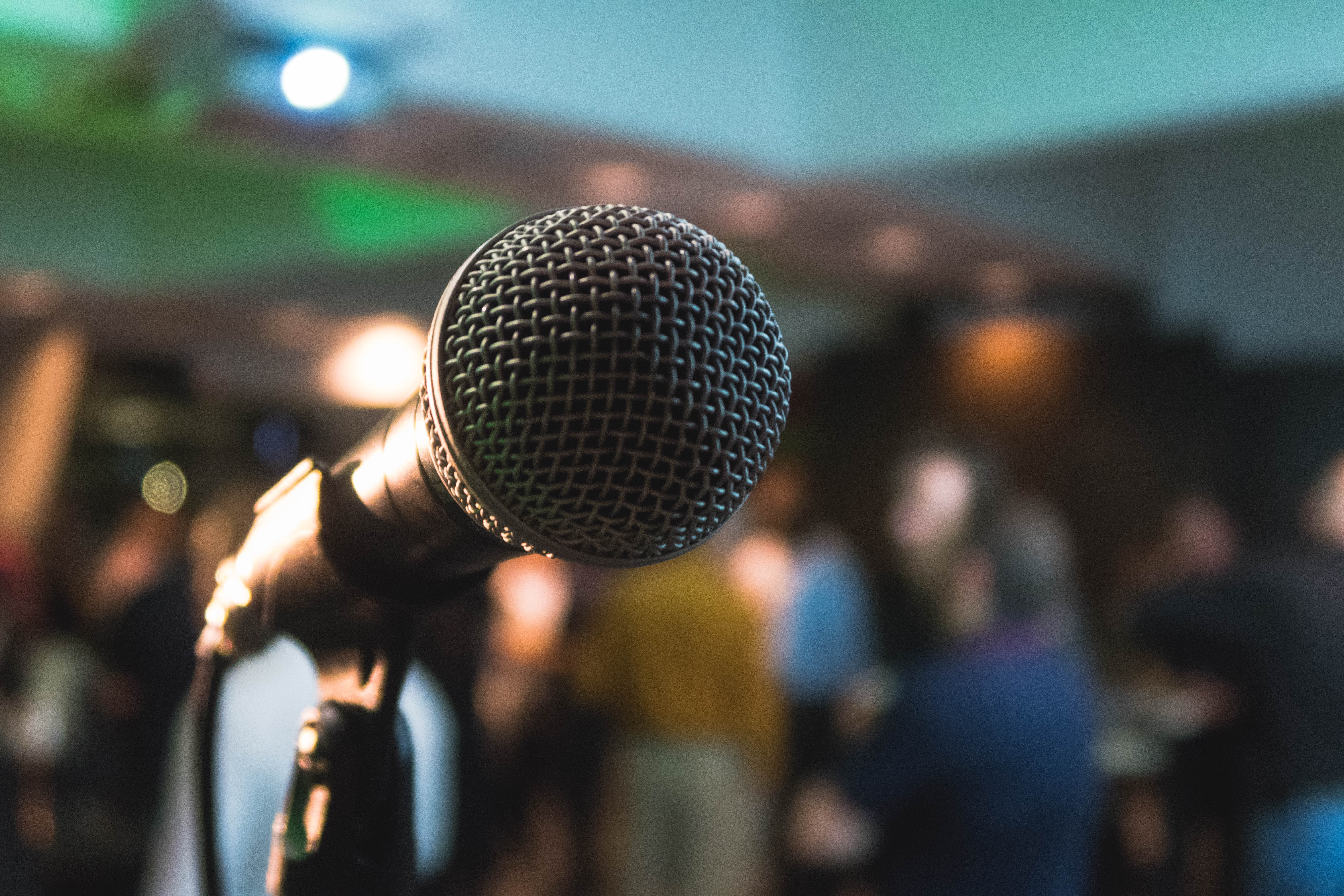 A microphone on a stand in front of a blurred-out crowd. Photo courtesy of Kane Reinholdtsen on Unsplash.
