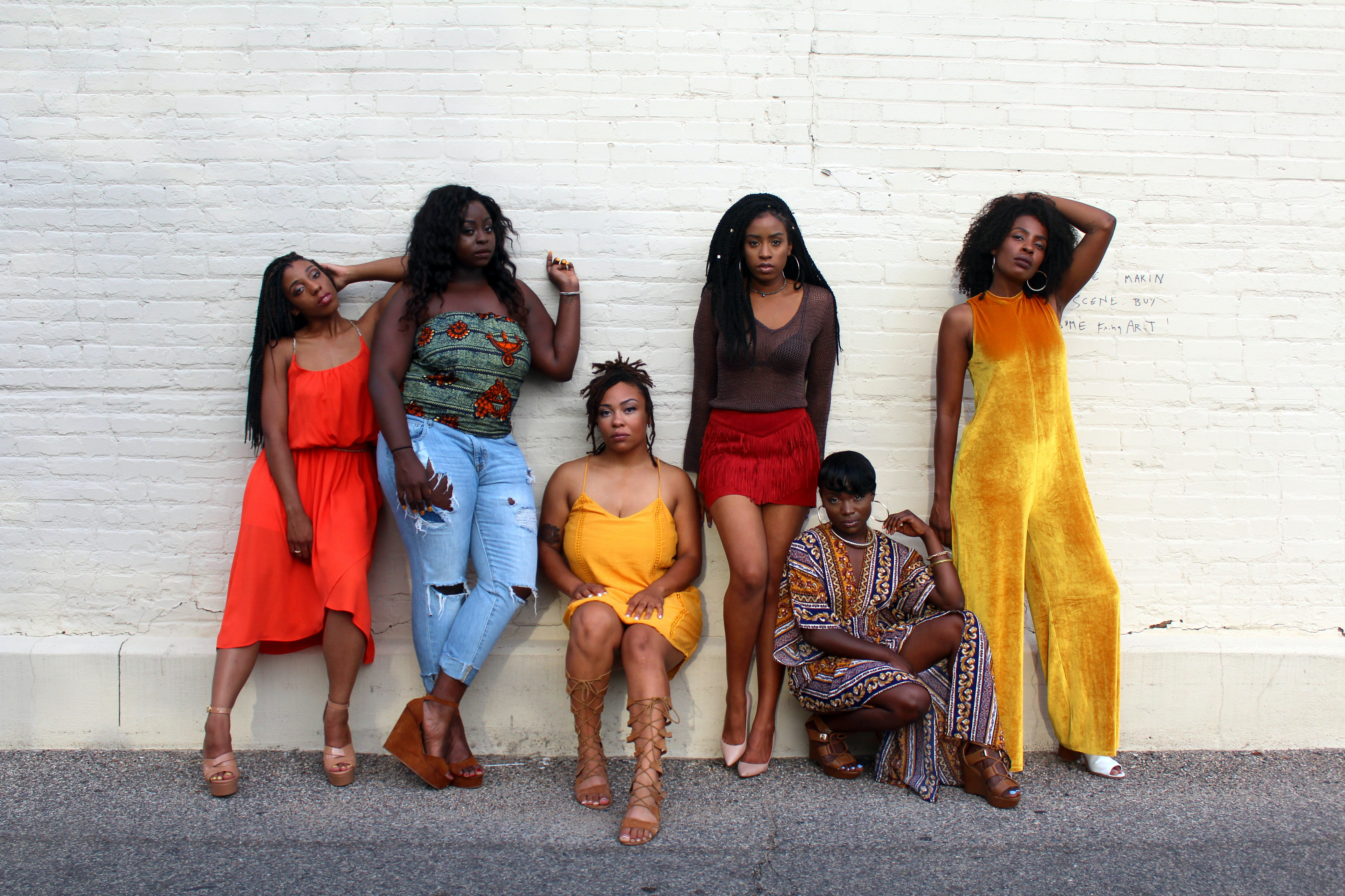 Six Black women wearing different styles of clothing leaning on a white brick wall. Photo courtesy of Clarke Sanders on Unsplash.