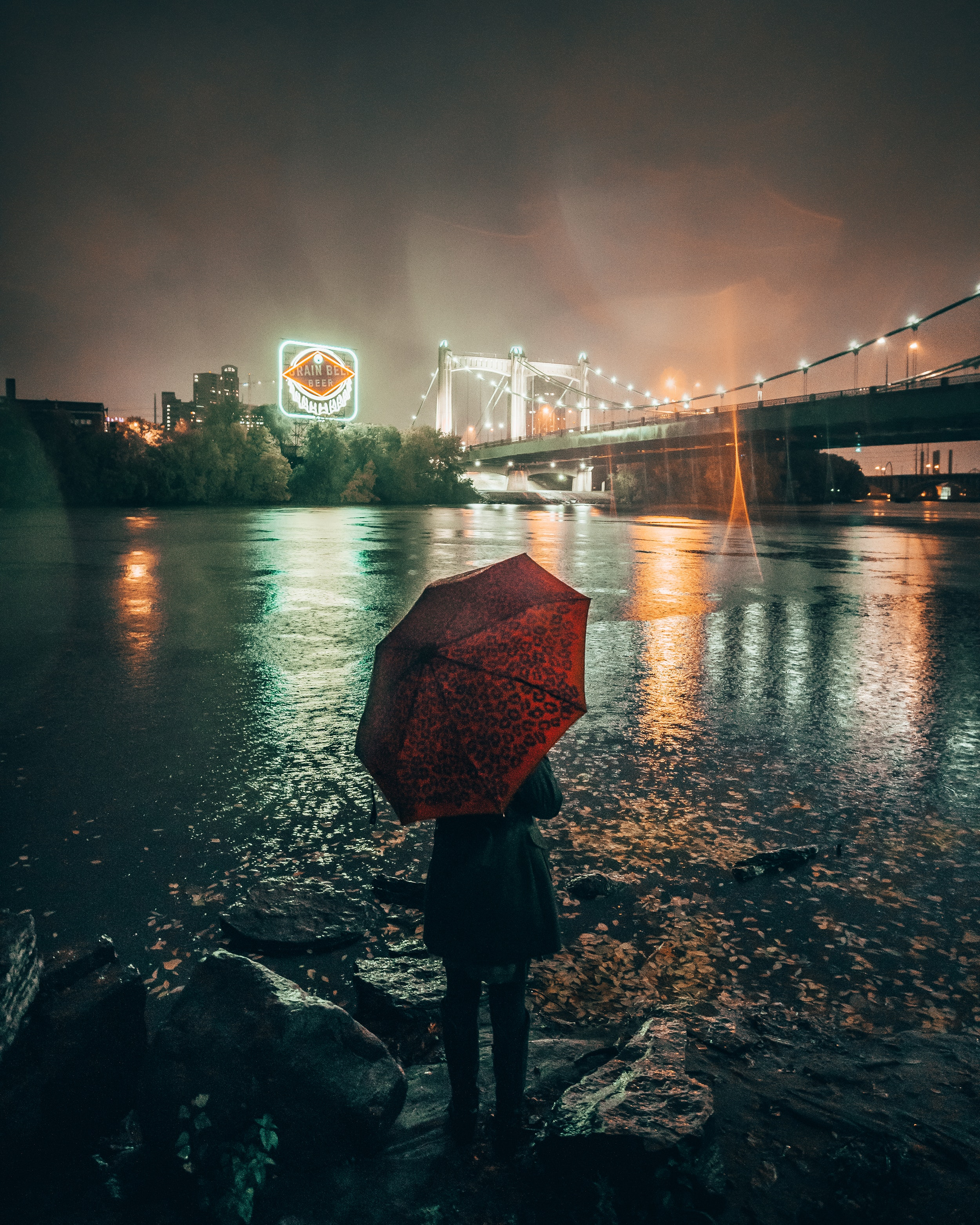A person standing alone in front of a city bridge in the dark and rain. Photo courtesy of Josh Hild on Pexels.
