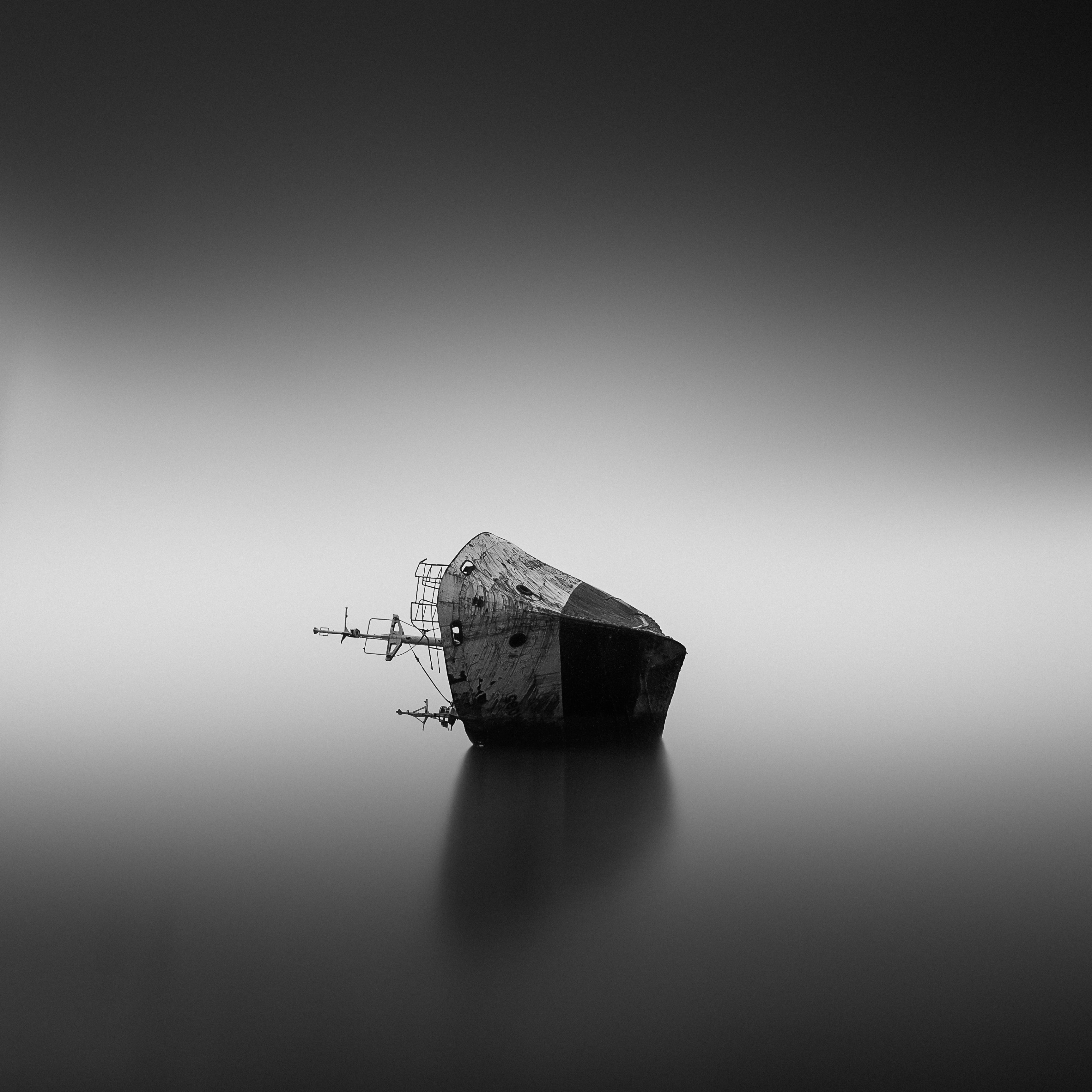 Black and white photo of a sinking ship on still water. Photo courtesy of Alwi Alaydrus on Unsplash.